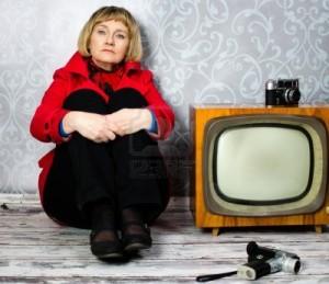 senora-de-mediana-edad-sentado-en-el-suelo-junto-al-viejo-televisor-retro-y-camara-de-fotos